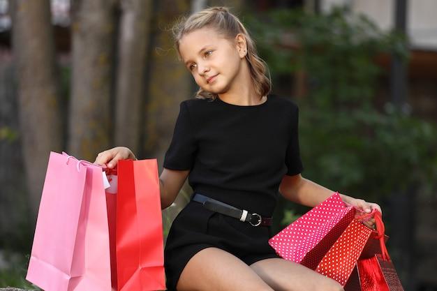 色付きのバッグを持って公園に座っている美しい少女