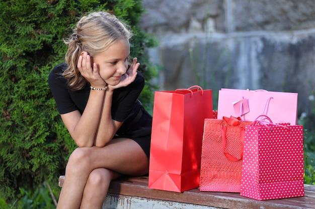 の美しい少女は、色付きのバッグと公園のベンチに座っています