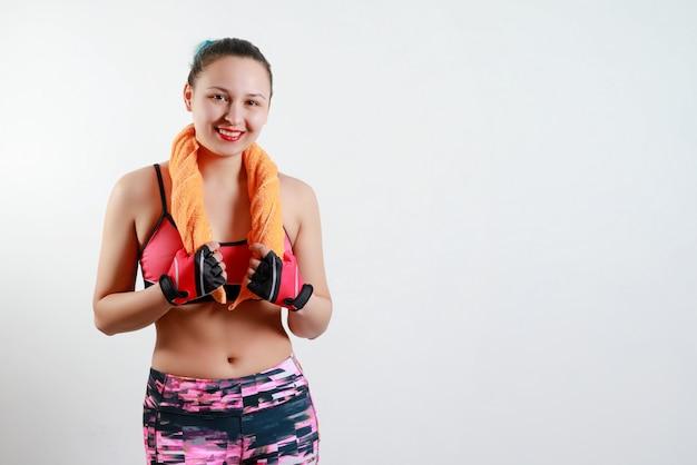 スポーツ服の美しい少女は、彼女の首に両手でタオルを持っています。白で隔離