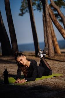 Красивая девушка в спортивной одежде, лежа на коврике в парке.