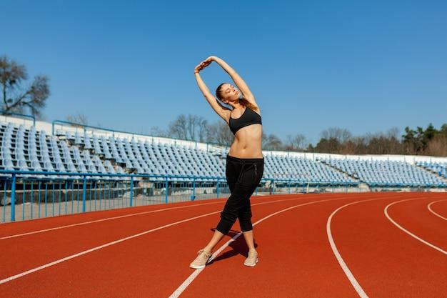 육상 트랙에 서있는 스포츠에서 아름 다운 소녀