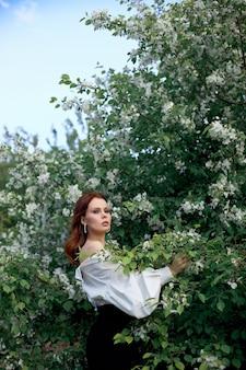 꽃 사과 덤 불의 가지에서 봄에 아름 다운 소녀. 밝은 여름날 여자의 초상화