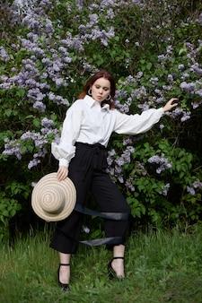 Красивая девушка весной в ветвях цветущих кустов сирени портрет женщины в яркий летний день