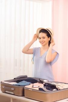 スタイリッシュな服と帽子の美しい少女は、自宅で旅行バッグを詰めながらポーズと笑顔です Premium写真