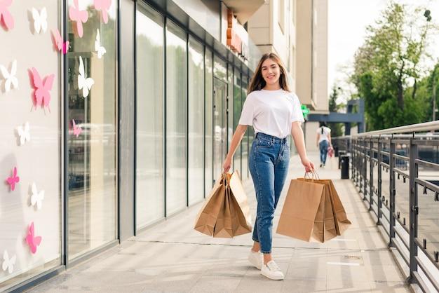 태양 안경에 아름다운 소녀는 쇼핑 가방을 들고 거리를 걷는 동안 웃고