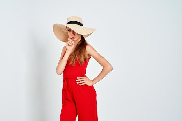 Красивая девушка в шляпе от солнца, стоя на белом фоне в студии в элегантном красном комбинезоне
