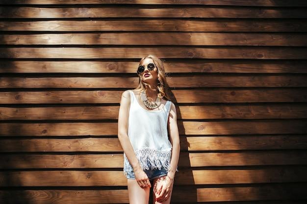 갈색 벽에 포즈를 취하는 선글라스를 쓴 아름다운 소녀