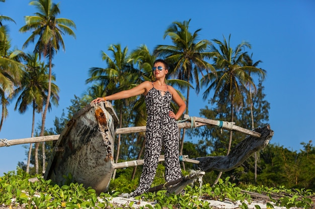 높은 야자수와 어선 근처 해변에서 포즈를 취하는 선글라스를 쓴 아름다운 소녀