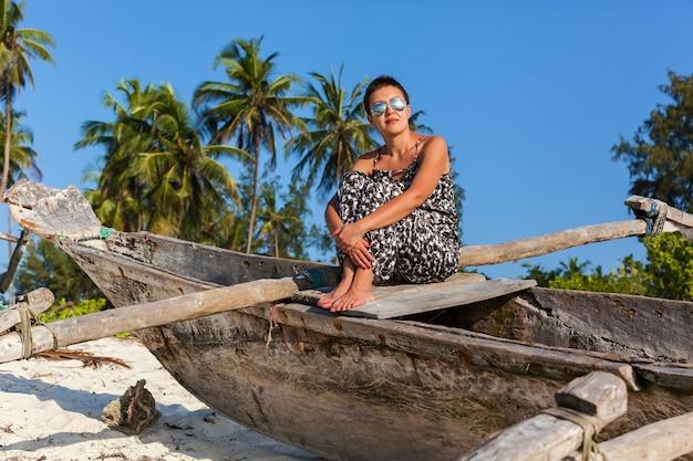 Красивая девушка в солнцезащитных очках позирует на пляже с пальмами и белым песком возле рыболовного бо