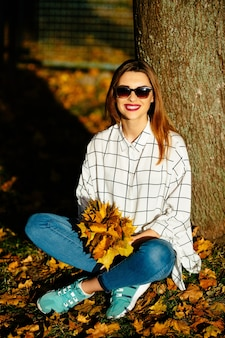 Beautiful  girl in sunglasses sits under the tree with  a bunch of autumn leaves