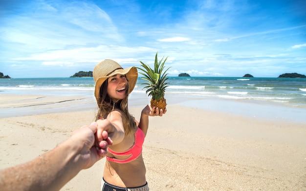 男の手を握ってビーチの上を歩く水着とパイナップルの美しい少女