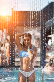 Красивая девушка в купальниках, принимая душ под водой на курортном пляже