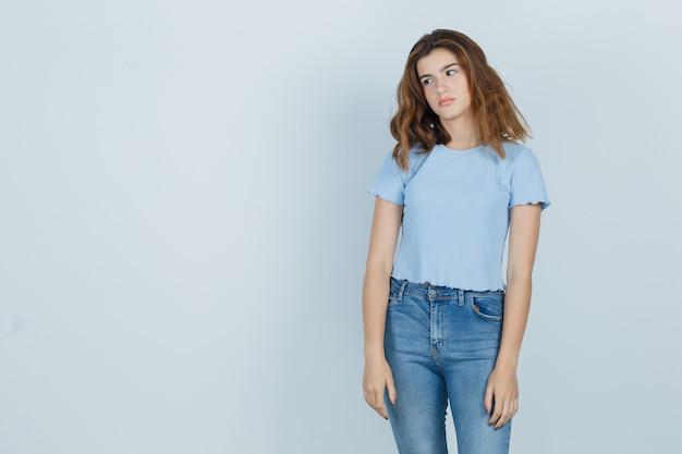 Красивая девушка в футболке, джинсах смотрит в сторону и выглядит усталой, вид спереди.