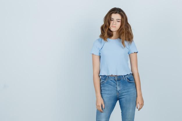 Красивая девушка в футболке, джинсах смотрит вниз и выглядит несчастной, вид спереди.