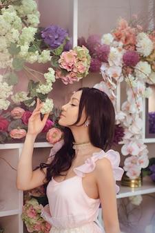 Красивая девушка в нежном розовом платье против цветочного в цветочном магазине. радостный