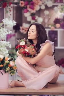 Красивая девушка в нежном розовом платье с букетом цветов пионов в руках, сидя на столе