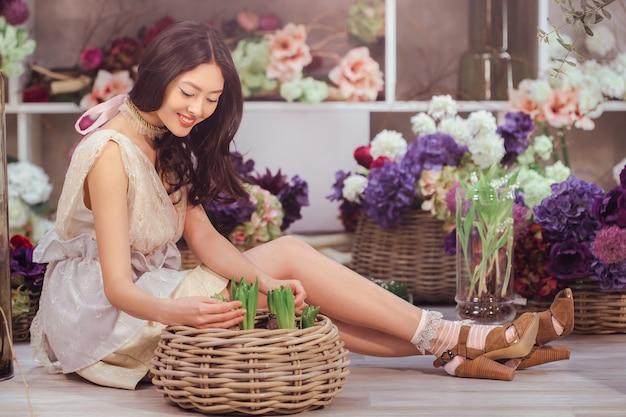 Красивая девушка в нежном белом платье сидит на полу против цветочного в цветке
