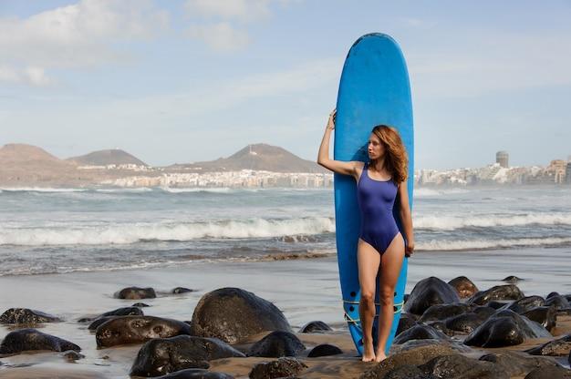 Красивая девушка в синем купальнике стоит с доской для серфинга над атлантическим океаном