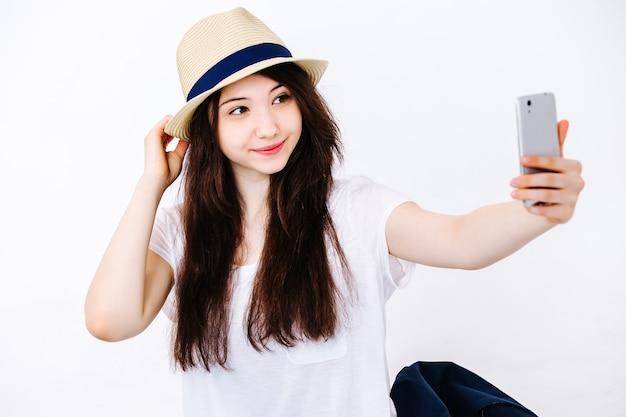 Красивая девушка в шляпе делает селфи на полу в студии на белой стене
