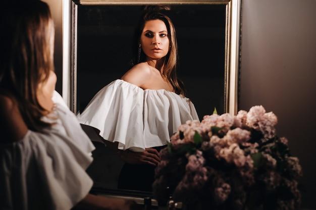 Красивая девушка в зеркальном отражении дома. девушка перед праздником возле домашнего зеркала. девушка в белом платье с длинными волосами собирается на вечеринку дома.