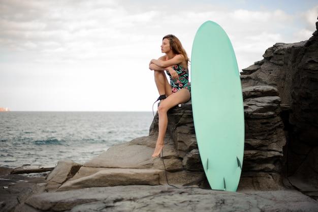 대서양과 맑은 하늘 위에 바위에 서핑 보드 근처에 앉아 멀티 컬러 수영복에서 아름 다운 소녀