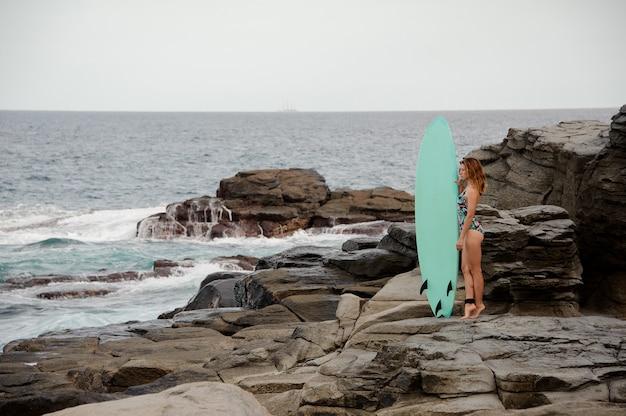 대서양의 바위 해변에서 서핑 보드와 함께 서있는 멀티 컬러 수영복에서 아름 다운 소녀