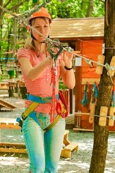 ロープで公園の美しい少女はアウトドアを達成します