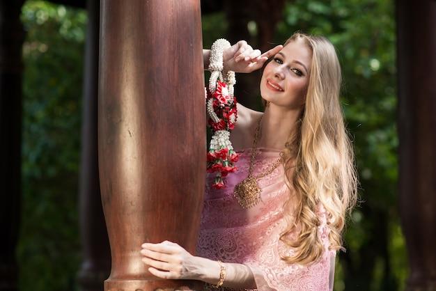 タイで東洋の化粧旅行でタイの国民の明るいドレスを着た美しい少女