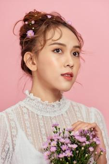 Красивая девушка в белом платье с цветами в руках на розовом