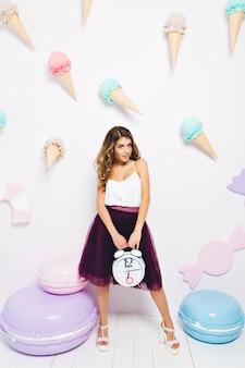 大きなおもちゃのマカロンの近くに立って、目覚まし時計を保持しているトレンディなバイオレットスカートで美しい少女。テーマパーティーでポーズスタイリッシュな服装でエレガントな若い女性の肖像画
