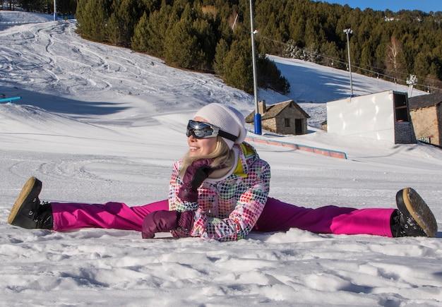 Красивая девушка в бечевке на снегу в удобной лыжной экипировке