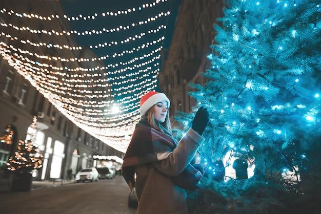 Красивая девушка в теплой одежде и новогодней шапке стоит ночью у елки на украшенной улице