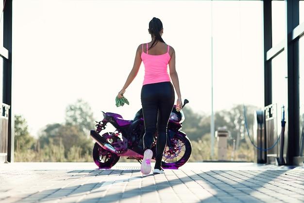 Красивая девушка моет мотоцикл и вытирает его от пены на автомойке самообслуживания