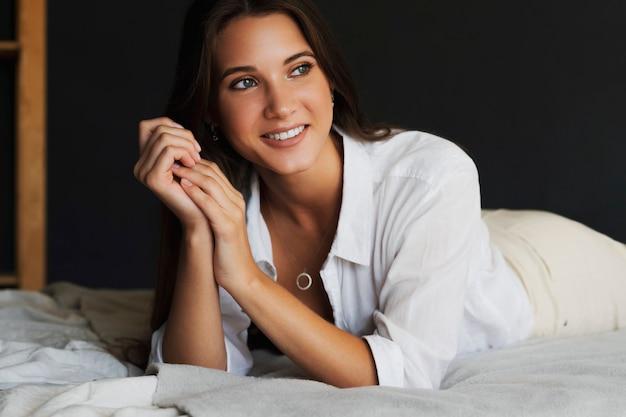 白い服を着た美しい少女が寝室のベッドに横たわっています。黒髪の笑顔の女性の肖像画をクローズアップ。
