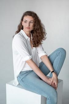 흰 옷을 입고 아름 다운 소녀는 바닥에 앉아있다.