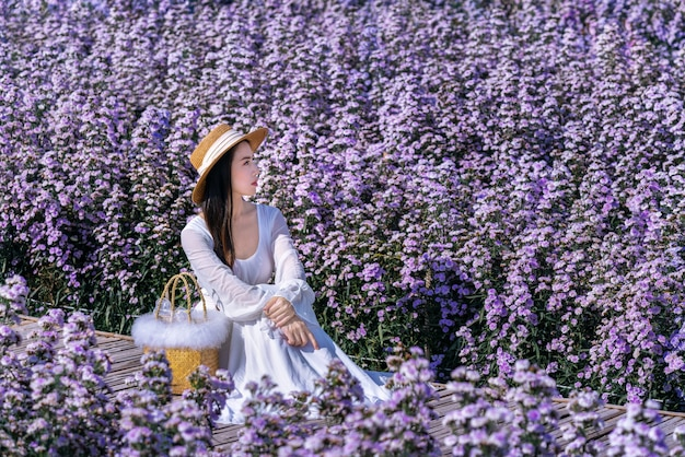 Красивая девушка в белом платье сидит в полях цветов маргарет