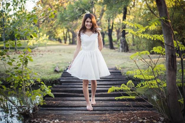 Красивая девушка в белом платье, ходить босиком по маленькому деревянному мосту через канаву