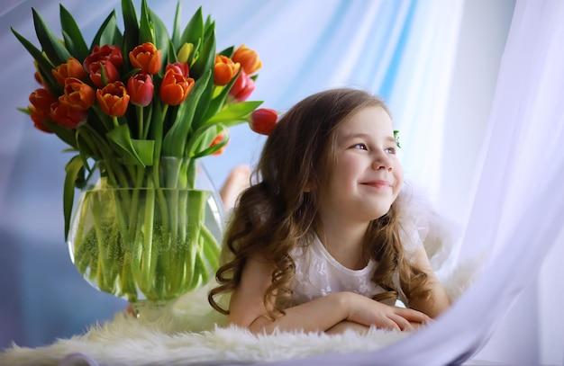 最初のチューリップの壮大な花束と白いドレスの美しい少女。国際婦人デー。チューリップの女の子。