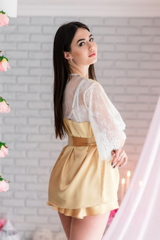 Красивая девушка в белом кружевном будуарном платье на фоне цветов декора с большим окном