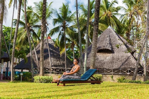 Красивая девушка в белой рубашке и солнечных очках позирует на пляже с высокими пальмами и белым песком возле рыбацкой лодки. африка момбаса побережье индийского океана