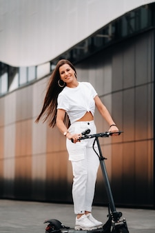 街の電動スクーターで白いスタイリッシュな服を着た美しい少女