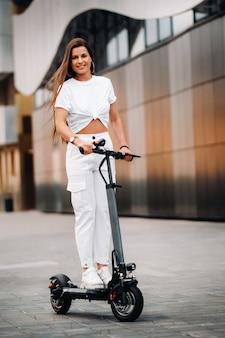 街の電動スクーターで白いスタイリッシュな服を着た美しい少女。