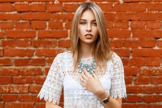 Красивая девушка в белой винтажной кружевной блузке с украшениями на фоне кирпичей