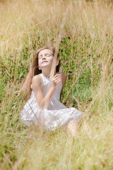 화창한 날 초원에서 쉬고 있는 야생화를 입은 아름다운 소녀