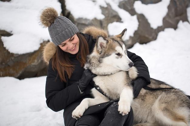 Красивая девушка в зимнем лесу с собакой. играйте с собакой сибирский хаски.