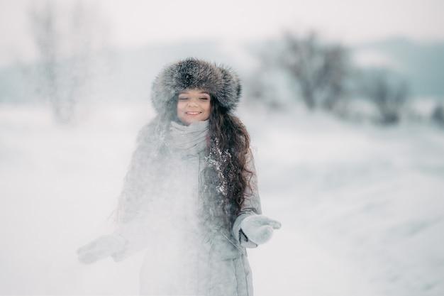 Красивая девушка в зимней меховой шапке улыбается играть со снегом