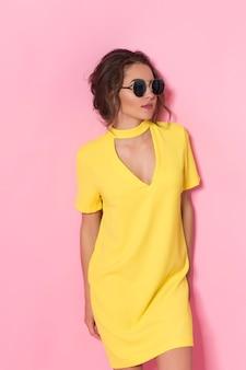 Красивая девушка в желтом платье в солнцезащитных очках позирует, улыбаясь на розовом фоне