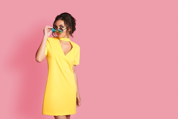 Красивая девушка в желтом платье в солнцезащитных очках позирует, улыбаясь на розовом пространстве в студии