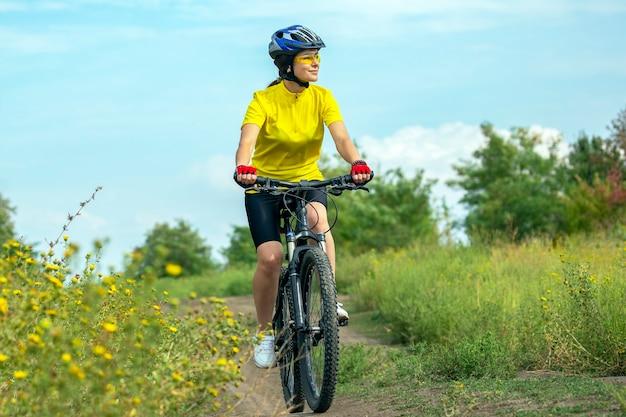 자연 속에서 자전거를 타고 노란색에서 아름 다운 소녀. 스포츠 및 레크리에이션. 취미와 건강.