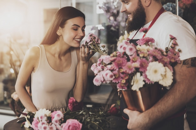 Beautiful girl inhales the scent of fresh flowers